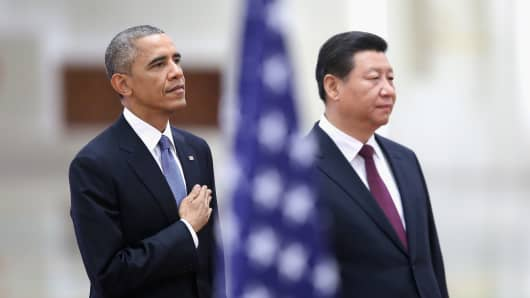 Chinese President Xi Jinping and U.S. President Barack Obama listen to their national anthems during a welcoming ceremony inside the Great Hall of the People in Beijing, China.