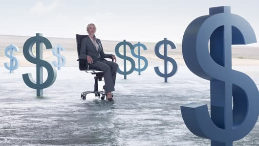 Businesswoman sitting in chair surrounded by dollar symbols