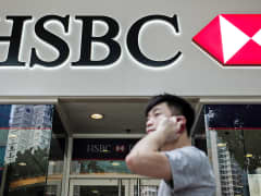 Man walks past HSBC bank branch