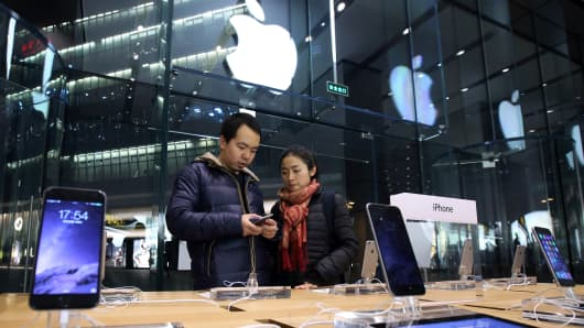 A couple look at an Apple Inc. iPhone 6 at an Apple store in the China Central Mall in Beijing, China, on Tuesday, Nov. 11, 2014.