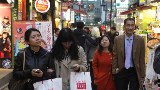 Shoppers walk in the Myungdong shopping district in Seoul, South Korea.