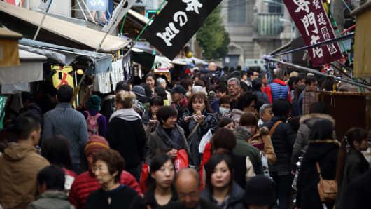 Customers walk outside Tsukiji Market in Tokyo
