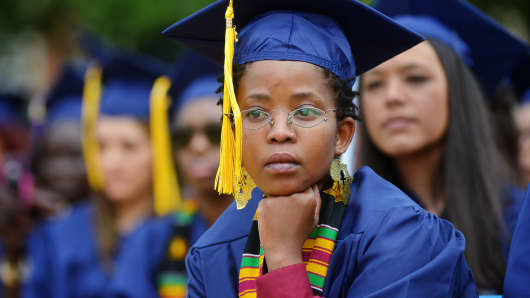 A graduate listens to the opening prayer during Howard University's commencement ceremonies on May, 10, 2014, in Washington, D.C.
