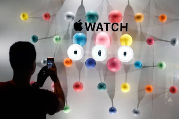 A man takes a picture of an Apple Watch window display in Paris.