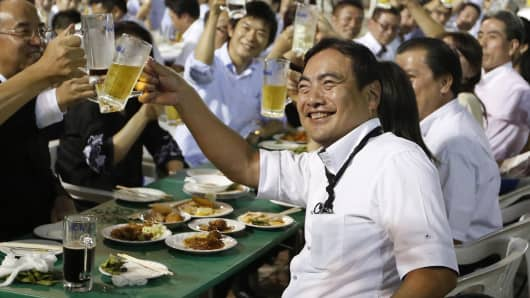 A group of Tokyo businessmen and businesswomen toast with mugs of beer at a beer garden in Tokyo.