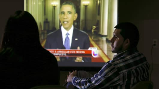A group of legal and undocumented immigrants watch U.S. President Barack Obama speaking about the country's immigration policy during a nationally televised address from the White House in Washington, on a screen in New Brunswick, New Jersey, November 20, 2014.