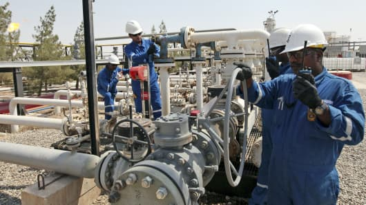 Workers check the valves at the Taq Taq oil field in Arbil, Iraq, in this Aug. 16, 2014 photo.