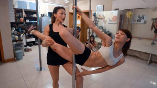 A pole dancing teacher conducting a class at her dance studio.