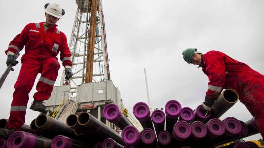 Workers prepare pipes used in the drilling of shale gas.