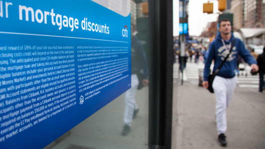 Pedestrians pass a sign advertising mortgages at a Citibank branch in New York.