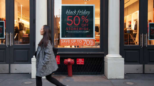 A pedestrian passes by a Black Friday discount sign at a Joe Fresh retail store in New York.