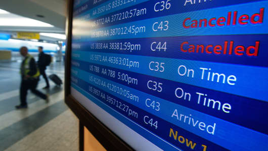 People walk past a sign board that announces canceled flights at LaGuardia airport on the day before Thanksgiving.