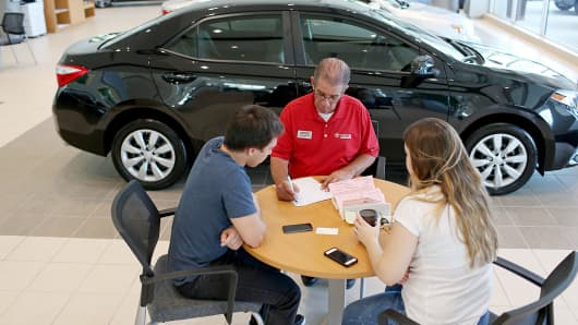 Salesman Jerry Holsman works with Erich Spin, left, and Anna Zatta at the Toyota of Deerfield dealership, in Deerfield Beach, Fla., Oct. 2, 2014.