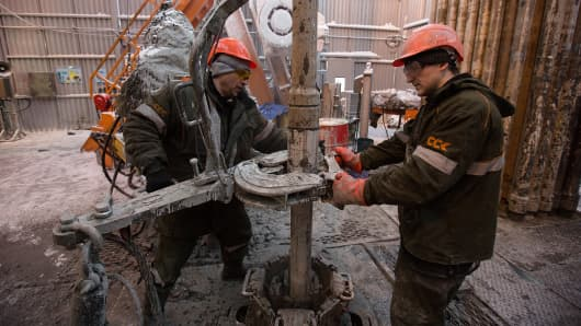 Workers use machinery to move drill sections on the drilling floor of the oil derrick in the Salym Petroleum Development oil fields near the Bazhenov shale formation in Salym, Russia.