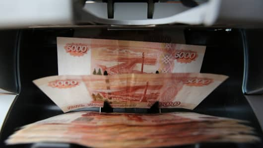 Five thousand Russian ruble banknotes pass through a money counting machine at a store in Moscow.
