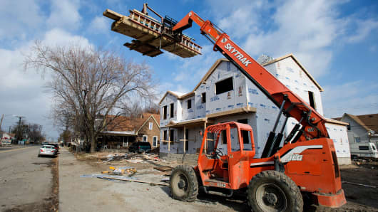 A SkyTrak telehandler holds building materials aloft at a residential housing construction site on Scotten Avenue in Southwest Detroit, Tuesday, Nov. 18, 2014.