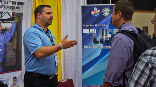 Patterson UTI Drilling representative, left, speaks with job seekers during the Eagle Ford Shale Job Fair in Corpus Christi, Texas.