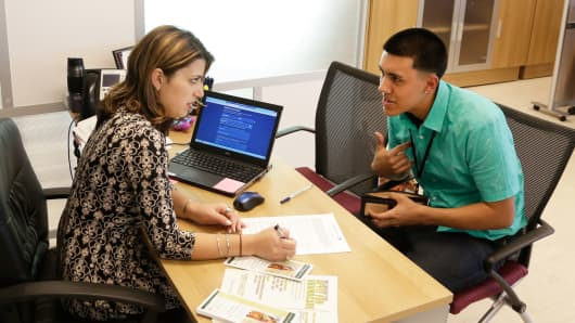 Navigator Dianelys Dominguez, left, assists Giovanny Vega, 18, of Miami, sign up for health insurance under the Affordable Care Act, Nov. 17, 2014, at the Borinquen Medical Center in Miami.