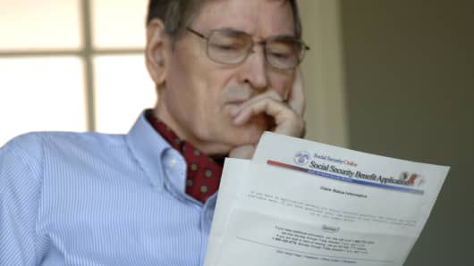 A man reads through a Social Security Benefits Application.