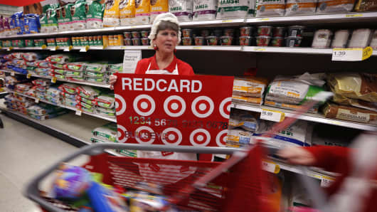 A Target employee promotes the store's Redcard debit and credit card to shoppers just after midnight on Black Friday, Nov. 28, 2014, in South Portland, Maine.