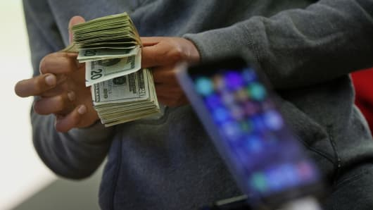A customer counts cash to pay for two iPhone 6 smartphones during the sales launch at an Apple store in New York.