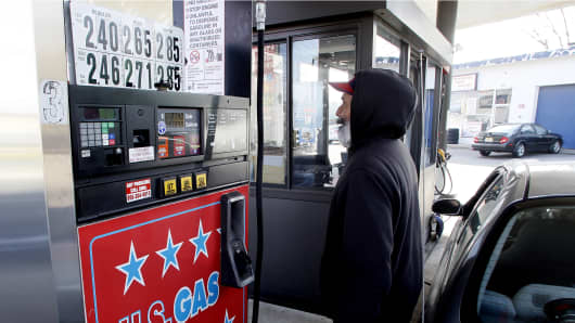 A gas station attendant fills a customer's vehicle in Turnersville, New Jersey December 4, 2014.