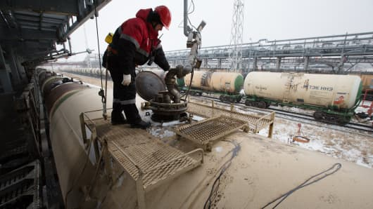 A worker overseas the loading of oil supplies into freight wagons at the Lukoil-Nizhegorodnefteorgsintez oil refinery, operated by OAO Lukoil, in Nizhny Novgorod, Russia.