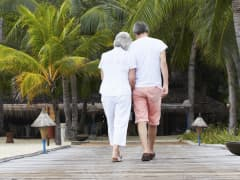 Senior couple walking on jetty in tropics