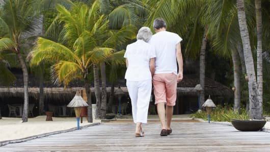 Senior couple walking on jetty in tropics