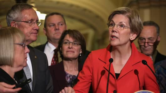Sen. Elizabeth Warren (D-Mass.) (5th L) speaks to members of the media as (L-R) Sen. Patty Murray (D-Wash.), Senate Majority Leader Sen. Harry Reid (D-Nev.), Sen. Jon Tester (D-Mont.), Sen. Amy Klobuchar (D-Minn.), and Sen. Charles Schumer (D-N.Y.) listen after a Democratic Senate leadership election at the U.S. Capitol Nov. 13, 2014.