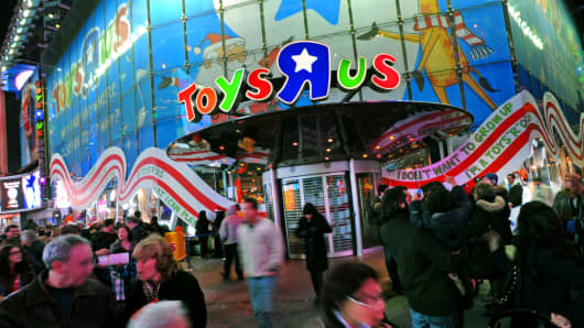 Pedestrians walk past a Toys R Us store in New York.