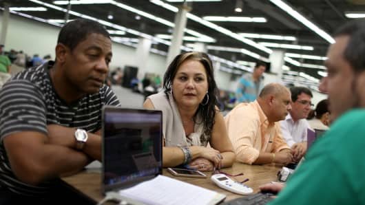 Heath-care applicants discuss plans available from the Affordable Care Act in Miami.