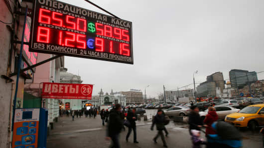 People walk past boards showing currency exchange rates in Moscow, December 17, 2014.