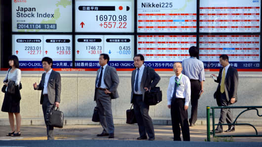 Pedestrians stand in front of stock market boards along the pavement in Tokyo, Japan.