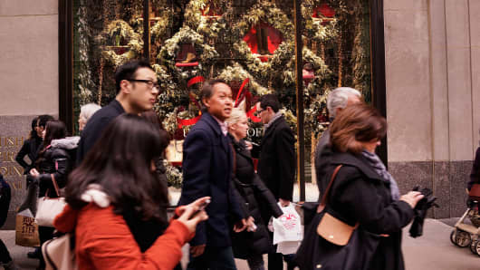 Shoppers walk along Fifth Avenue on December 17, 2014 in New York City.