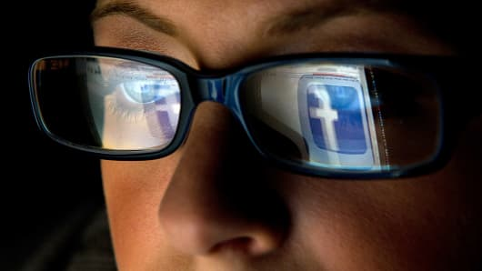 The Facebook logo is reflected in the eyeglasses of a user in San Francisco.