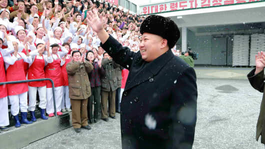 North Korean leader Kim Jong Un waves to workers during a visit to the Pyongyang Children's Foodstuff Factory in this undated photo released by North Korea's Korean Central News Agency (KCNA) in Pyongyang December 16, 2014.