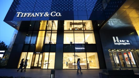 Pedestrians walk past a Tiffany & Co. store as it stands illuminated at night in Shanghai, China.
