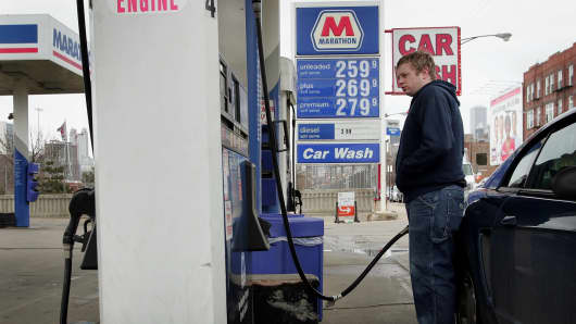 File photo of a man putting gas into his Mustang at a Marathon gas station in Chicago.