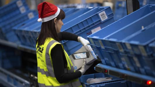 An employee wears a festive hat as she re-packs a tablet device on the semi-automated processing line at an Argos goods distribution center, operated by Home Retail Group in the U.K.