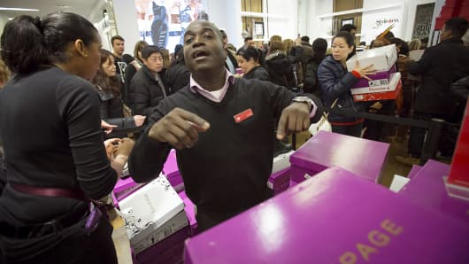 A sales assistant helps customers in the shoe department of Macy's in New York, Nov. 27, 2014.