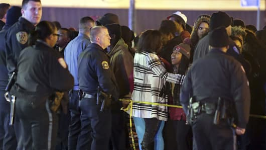 Police hold back a crowd at the perimeter of a scene following a shooting Tuesday at a gas station in Berkeley, Missouri.