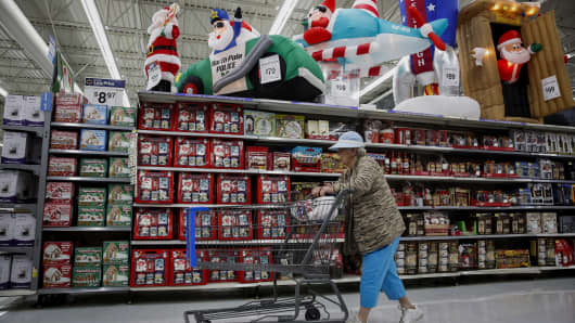 A woman pushes a shopping cart past Christmas decorations displayed for sale at a Wal-Mart.