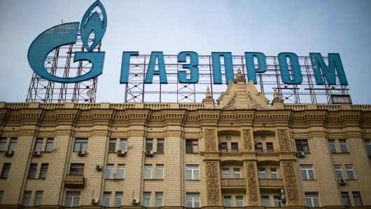A giant sign for OAO Gazprom stands above a building in Moscow, Russia