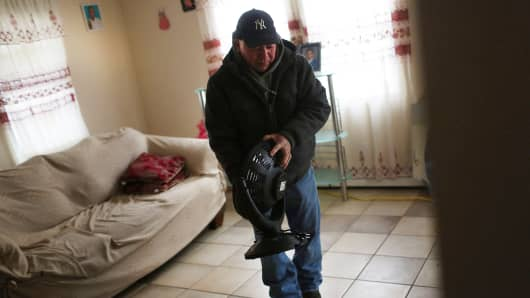 A man holds an electric heater in his freezing apartment in the Rockaways after losing heat following Hurricane Sandy on January 25, 2013 in New York City.