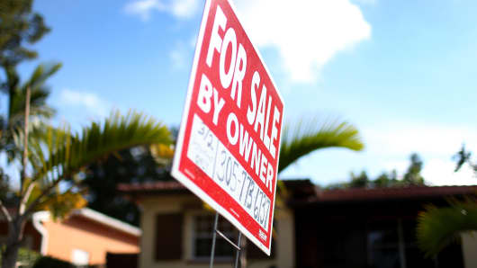"""A """"for sale"""" sign is seen in front of a home in Miami."""