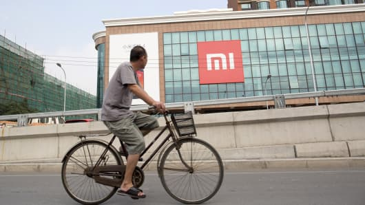 A man rides a bicycle past the Xiaomi offices in Beijing.