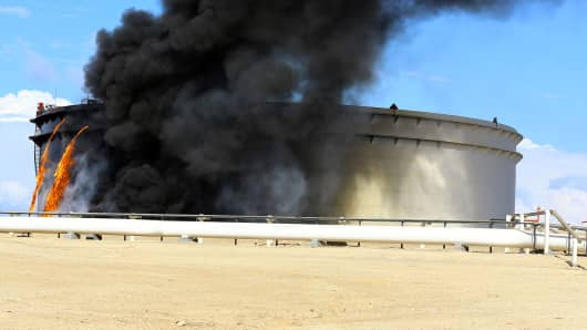 Black smoke billows out of a storage oil tank in the port of Es Sider in Ras Lanuf December 25, 2014. A rocket hit a storage tank at the eastern Libyan oil of port Es Sider as armed factions allied to competing governments fought for control of the country's biggest export terminal, officials said on Thursday.