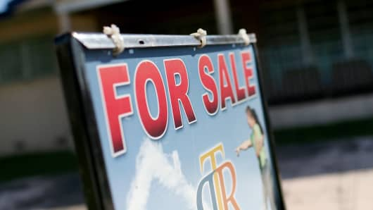 A for sale sign in front of a home in Miami.