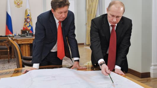 Russia's President Vladimir Putin (R) speaks with Russian gas monopoly Gazprom CEO Alexei Miller.